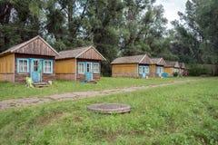 Rudern Sie mit hölzernen Sommerhäusern für Touristen am Iskra-Zeltplatz im Dorf von Shushenskoye lizenzfreie stockbilder