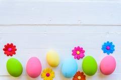Rudern Sie Ostereier mit bunten Papierblumen auf hellem Rosa und w lizenzfreies stockfoto