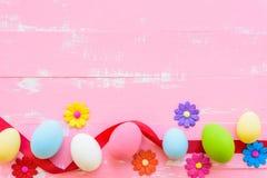 Rudern Sie Ostereier mit bunten Papierblumen auf hellem Rosa und w lizenzfreies stockbild