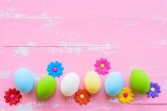 Rudern Sie Ostereier mit bunten Papierblumen auf hellem Rosa und w lizenzfreie stockfotografie