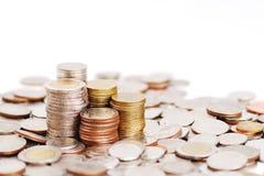 Rudern Sie Stapel Münzen auf Hintergrund vieler Münzen Stockbilder