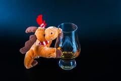 Rudolph ren med ett enkelt exponeringsglas för maltwhisky, symbol av Chr Royaltyfri Fotografi