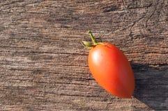 Rudopomarańczowy, mały pomidor na drewnianym tle; horyzontalna fotografia, przedmiot w kącie fotografia stock