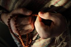 Rudraksha beads in men`s hands in traditional indian shawl. Man counting religious beads in sunlight. Religion and pray background Royalty Free Stock Image