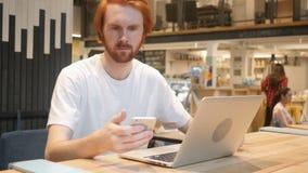 Rudzielec brody mężczyzna Używa Smartphone w kawiarni, Pisać na maszynie SMS zbiory