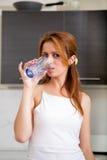 Rudzielec dziewczyna pije w kuchni zdjęcie royalty free