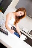 Rudzielec dziewczyna pracuje w kuchni fotografia stock