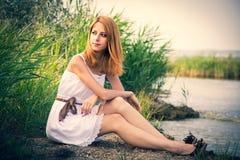 Rudzielec dziewczyna siedzi blisko rzeki fotografia royalty free