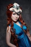 Rudzielec dziewczyny bajecznie spojrzenie, błękit długa suknia, jaskrawy makeup i duże rzęsy, Tajemnicza czarodziejska kobieta z  Fotografia Royalty Free