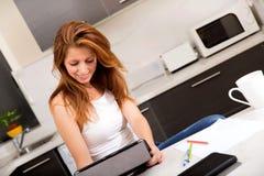 Rudzielec dziewczyny mienia pastylki komputer osobisty w kuchni Obraz Royalty Free