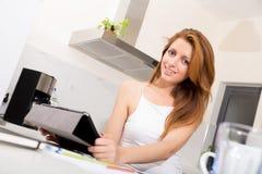 Rudzielec dziewczyny mienia pastylki komputer osobisty w kuchni Zdjęcie Royalty Free