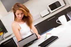 Rudzielec dziewczyny mienia pastylki komputer osobisty w kuchni fotografia stock