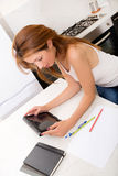 Rudzielec dziewczyny mienia pastylki komputer osobisty w kuchni Zdjęcia Stock