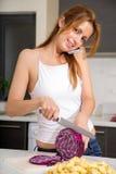 Rudzielec dziewczyny przecinanie w kuchenny telefonować fotografia royalty free