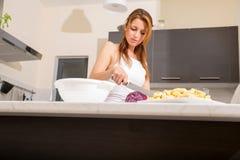 Rudzielec dziewczyny przecinanie w kuchni zdjęcia royalty free