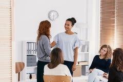 Rudzielec kobieta wspiera smutnego przyjaciela podczas psychotherapy spotkania grupowego obrazy royalty free