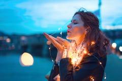 Rudzielec kobiety dosłania buziak z czarodziejskiego światła girlandą przy nocą Zdjęcia Stock