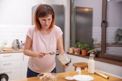 Rudzielec kobiety kucharstwo w kuchni Gospodyni domowej mienia łyżka w jej ręce Jedzenie i zdrowia pojęcie obrazy royalty free
