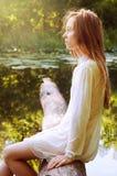 Rudzielec kobiety obsiadanie na drzewnej barkentynie blisko rzeki Obraz Royalty Free