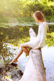 Rudzielec kobiety obsiadanie na drzewnej barkentynie blisko rzeki Fotografia Stock