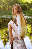 Rudzielec kobiety obsiadanie na drzewnej barkentynie blisko rzeki Obrazy Stock