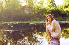 Rudzielec kobiety obsiadanie na drzewnej barkentynie blisko rzeki Zdjęcie Stock