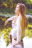 Rudzielec kobiety obsiadanie na drzewnej barkentynie blisko rzeki Zdjęcie Royalty Free