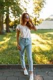 Rudzielec modnisia piękna młoda kobieta w eleganckiej koszulce w modnych cajgach w modnych okularach przeciwsłonecznych w białych zdjęcie royalty free