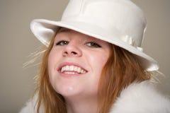 Rudzielec ono uśmiecha się w białym odczuwanym futerku i kapeluszu Obrazy Stock