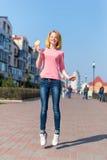 Rudzielec pięknej młodej kobiety skokowa wysokość w powietrzu nad niebieskim niebem trzyma kolorowego lizaka Ładna dziewczyna ma  obraz stock