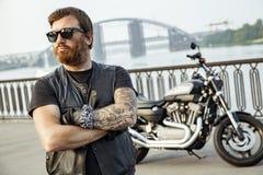 Rudzielec rowerzysta z brodą w skórzanej kurtki pozyci z krzyżujący obraz royalty free