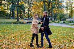 Rudzielec samiec i blondynki kobieta ma zabawę w jesieni miasta parku Zdjęcie Stock