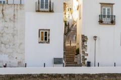 Rue étroite ascendante entre deux maisons blanches dans Tavira, Portugal photographie stock
