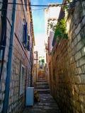 Rue étroite de vieille ville avec des escaliers, des portes, des fenêtres et des guirlandes Croatie de fleur photographie stock libre de droits