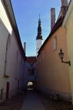 Rue étroite médiévale à Tallinn avec une lanterne sur le mur et une église dans l'avant, Estonie Photographie stock