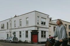 Rue anglaise typique à Brighton, et fille croisant la scène montant une bicyclette image stock