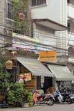 Rue asiatique habituelle avec les couples des motocyclettes Image libre de droits