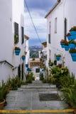 Rue avec des échelles décorées des fleurs et des taches au village espagnol traditionnel blanc Mijas Photographie stock libre de droits