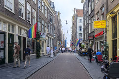 Rue avec le drapeau gai d'arc-en-ciel à Amsterdam Photographie stock