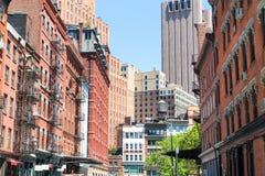 Rue avec les immeubles de brique et le gratte-ciel image stock
