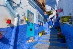 Rue bleue avec des pots de couleur dans Chefchaouen Photos stock