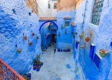 Rue bleue avec des pots de couleur dans Chefchaouen Image libre de droits