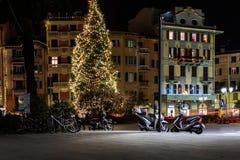 Rue centrale de nuit avec l'arbre de Noël et motocyclettes garées sous lui Image libre de droits