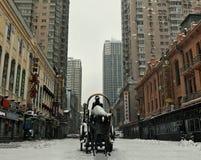 rue chinoise couverte de neige et moderne avec un monument Privation de monument avec un cavalier sur une rue chinoise avec tours photos stock