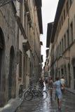 Rue d'étroit de ville de Florence avec les bicyclettes garées Photographie stock libre de droits