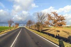 Rue dans les terres cultivables dans le coucher du soleil Photo stock