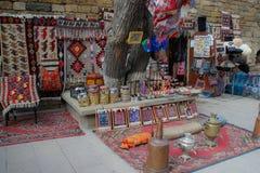 Rue de la vieille ville avec les tapis azerba?djanais traditionnels sur le mur et le vendeur photographie stock