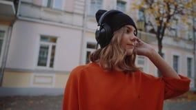 Rue de marche mignonne de jeune fille entre les bâtiments et la musique de écoute dans des écouteurs, style urbain, années de l'a banque de vidéos
