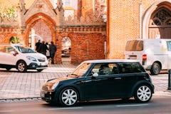 Rue de Mini Cooper Car Moving At de couleur verte avec le conducteur femelle Photographie stock libre de droits
