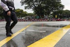 Rue de passage de promenade de policier avec des personnes tenant le drapeau de Singapour pour l'enterrement de M. Lee Kuan Yew Photo stock